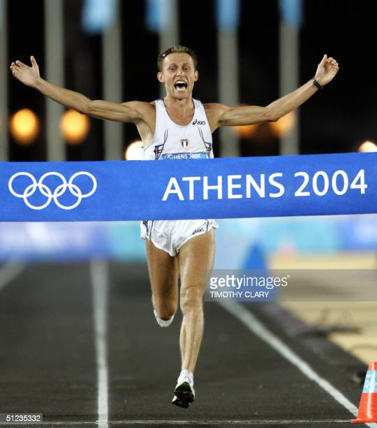 Men's marathon winner Stefano Baldini of Italy crosses the finish line as he arrives in the Panathinaiko Stadium in Athens 29 August 2004. The Men's...