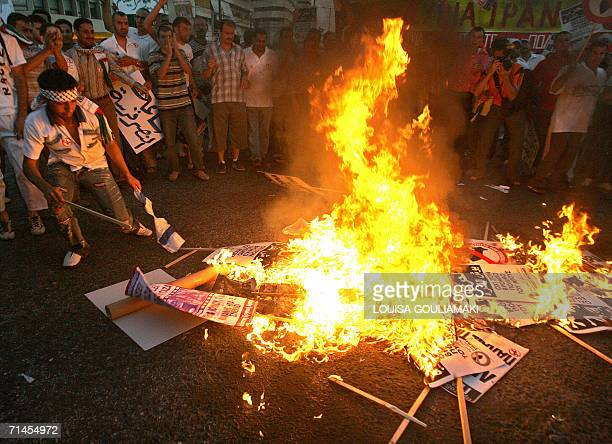 Muslim demonstrators burn Israeli flags and posters with a portrait of US President George W Bush in front of the Israeli embassy in Athens 15 July...