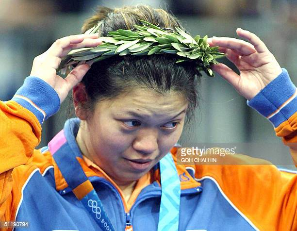 Netherlands' silver medalist Mia Audina adjusts her laurel during the medal ceremony of the women's singles of the Olympic Games badminton...