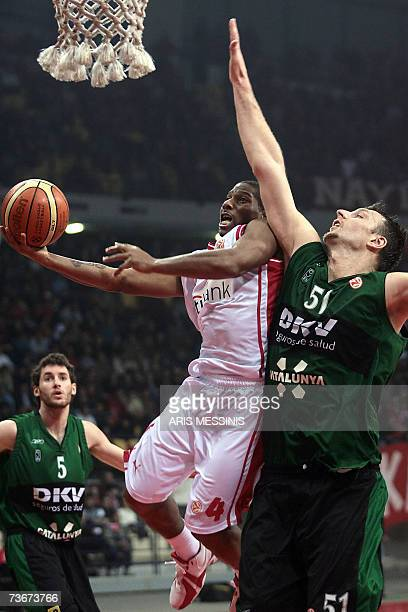 Olympiakos' James Penn jumps to score as Juventut Badalona's Andy Betts tries to stop him during their Euroleague basketball top 16 basketball game...