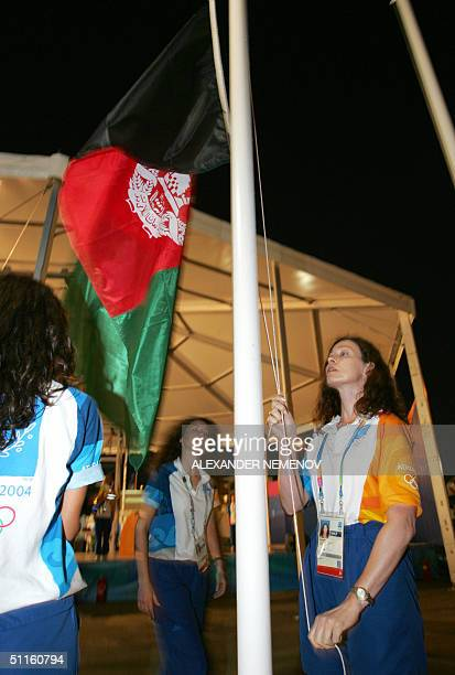 Olympic staff raise the Afghan national flag at the Olympic village in Athens, 11 August 2004, two days before the opening of the summer games. AFP...