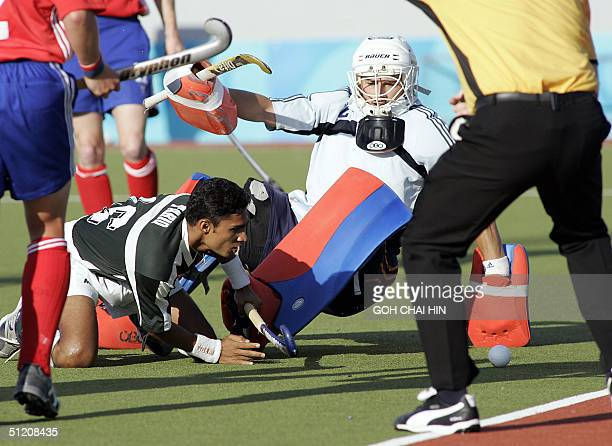 Pakistan's Tariq Aziz goes down to get the ball past Britain's goalkeeper Jimi Lewis in first half action of the Olympic Games hockey competition in...