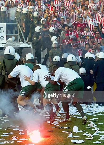 Players of Greek football club Panathinaikos cower behind riot police for protection from objects and flares thrown by rival Olympiakos Piraeus fans...