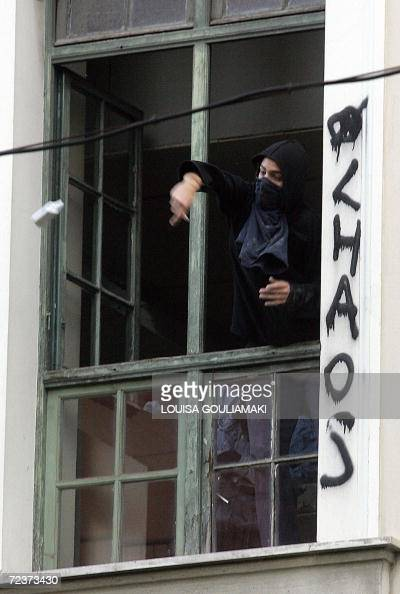 Protestors throw stones from the windows of the the Athens