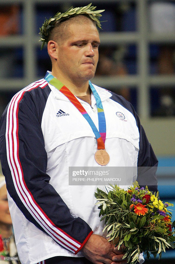 Rulon Gardner stands on the podium during the men's Greco-Roman 120 kg medals ceremony of the 2004 Olympic Games 25 August 2004 in Athens. Former Olympic champion Gardner announced his retirement after Russia's Khasan Baroev took his superheavyweight Greco-Roman wrestling title.