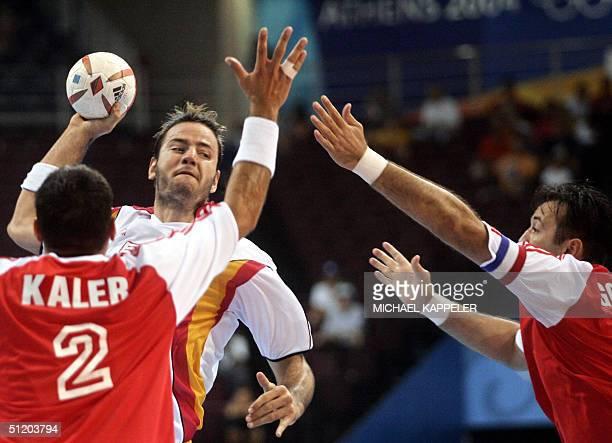 Spain?s Iker Romero attempts to score while Croatia?s Niksa Kaleb and Slavko Goluza tries to stop him during their Olympic Games handball preliminary...