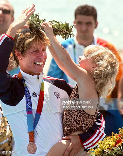 Sydney the daughter of American bronze winner Susan Williams removes the olive wreath off her head as she stands on the podium 25 August 2004 in...