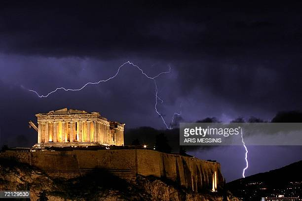 The ancient Greek Parthenon temple, atop the Acropolis hill overlooking Athens, is framed by lightning bolts during a thunderstorm that broke out in...