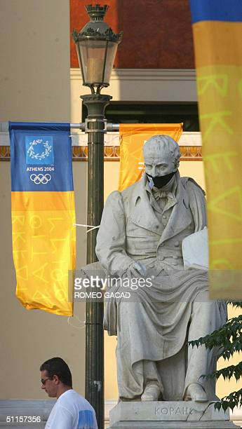 The monument of Greek classical scholar Adamantios Korais outside the Athens University is gagged with black cloth following a protest by a local...