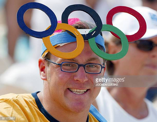 Tobias from Muenster in Germany watches the games wearing Olympic rings on his head, 15 August 2004 at the Markopoulo Olympic Equestrian Centre in...