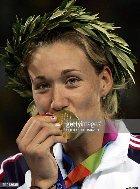 Beach volley player Kerri Walsh kisses her gold medal after she and her teammate Misty May won over Brazilian Adriana Behar and Shelda Bede, 24...