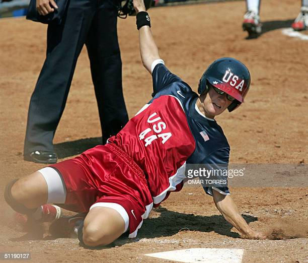 US centerfielder Laura Berg slides into home plate scoring the first run for her team in the third inning of their preliminary round softball game...