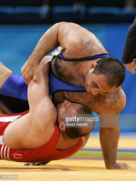 Uzbekhistan's Artur Taymazov fights with Iran's Alireza Rezaei during their men's 120 kg final competition at the 2004 Olypmic Games in Athens 28...