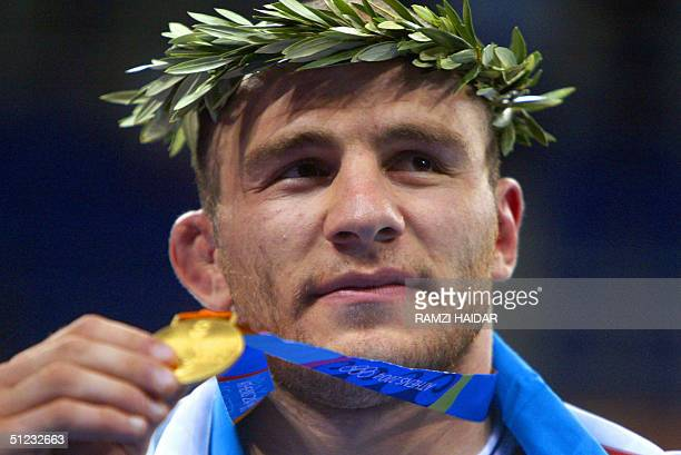 Uzbekistan's Artur Taymazov displays his gold medal in the men's 120 kg free style wrestling competition of the 2004 Olypmic Games in Athens 28...