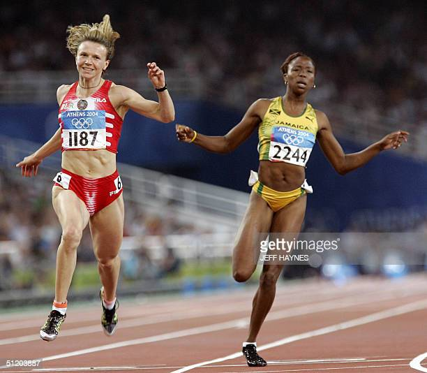 Yuliya Nesterenko of Belarus and Sherone Simpson of Jamaica compete in the women's 100m finals 21 August 2004 during the Olympic Games athletics...