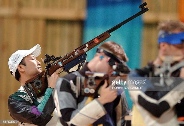 Zhanbo Jia of China adjusts his stance beside Mathew Emmons of the US in the final round in the Men's 50m Rifle 3 Positions competition during the...