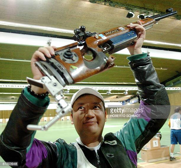 Zhanbo Jia of China holds his rifle high after winning the Men's 50m Rifle 3 Positions competition in the Athens 2004 Olympics at the Markopoulo...