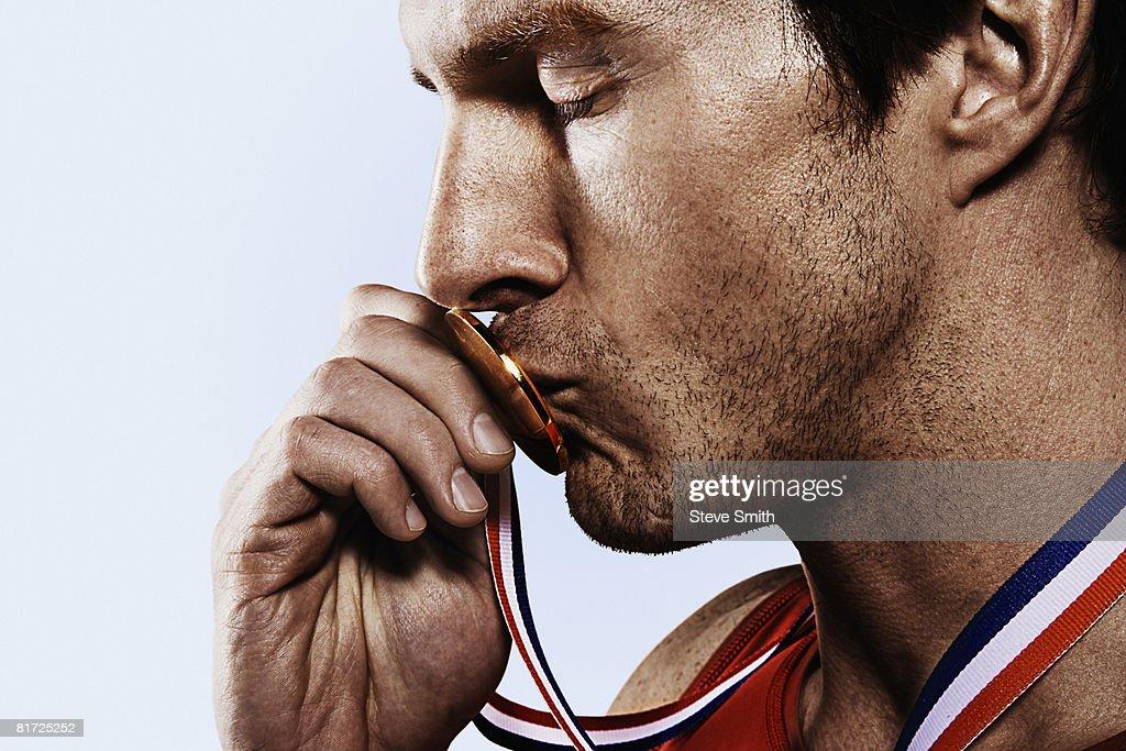 Athete kissing gold medal : Stock-Foto
