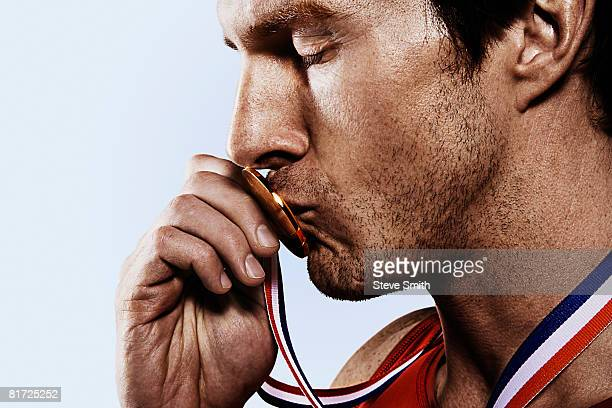 athete kissing gold medal - medal stock pictures, royalty-free photos & images