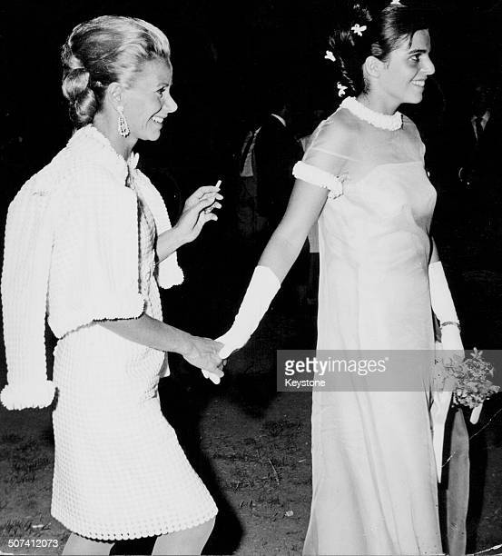 Athina Livanos Blandford and her daughter Christina Onassis holding hands as they attend a society wedding in Athens circa 1970