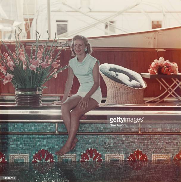 Athina Livanos Onassis the first wife of Greek shipowner Aristotle Onassis relaxing by the swimming pool aboard their yacht the 'Christina' in Monte...