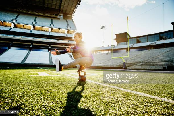 Athlete balancing on kettlebell while training