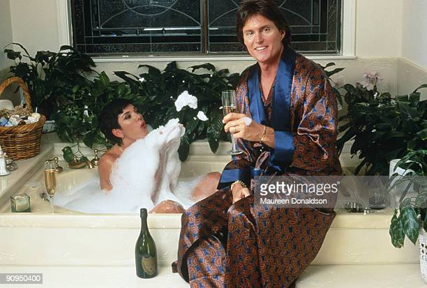 Athlete Bruce Jenner and his partner Kris Jenner, formerly Kris Kardashian, share a bottle of Dom Perignon over a bubble bath, circa 1991.
