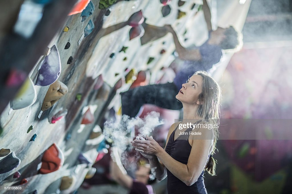 Athlete chalking her hands at rock wall in gym : Stock Photo
