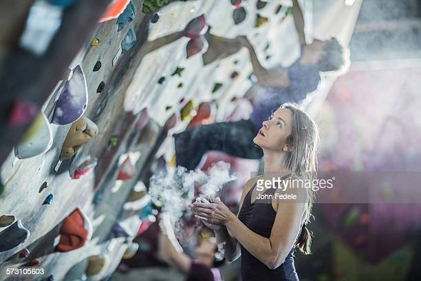 Athlete chalking her hands at rock wall in gym