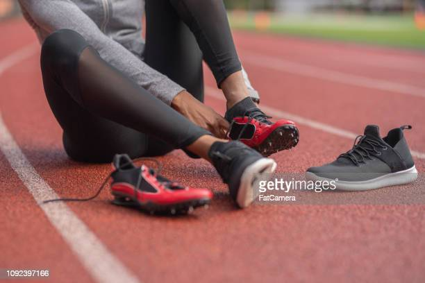 athlete changes into her track shoes on a stadium field - studded stock pictures, royalty-free photos & images