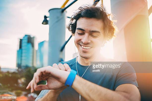 athlete checking his smart watch - checking sports stock pictures, royalty-free photos & images