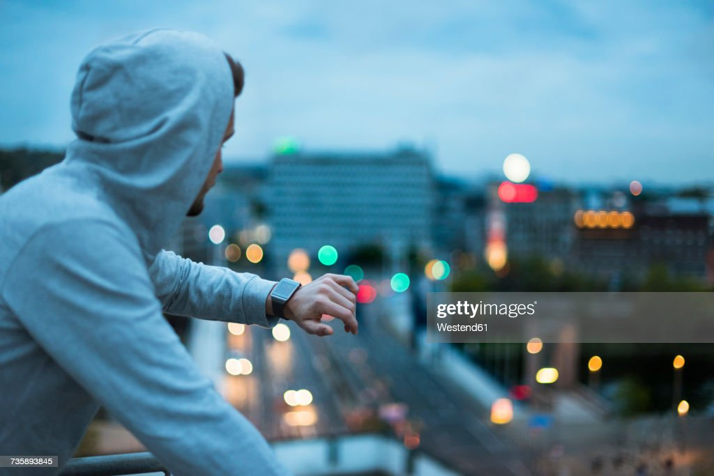 Athlete checking his smartwatch above the city at dawn : Stock-Foto