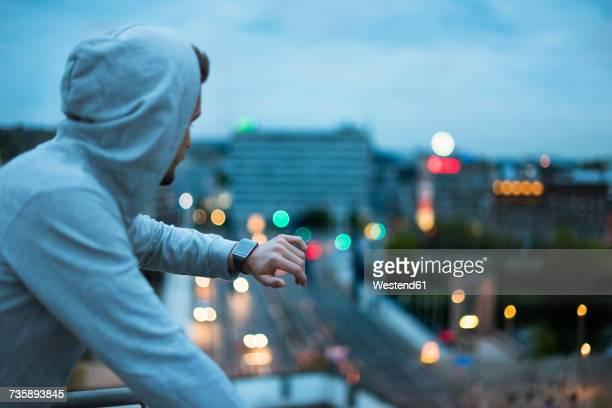 athlete checking his smartwatch above the city at dawn - checking sports stock pictures, royalty-free photos & images