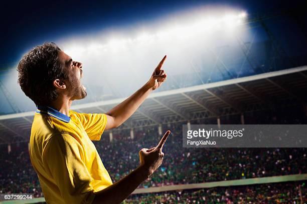 Athlete cheering with excitement in sports stadium arena