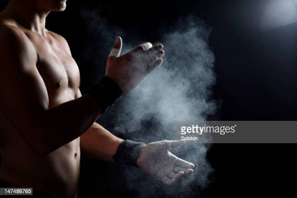 Athlete clapping hands with chalk dust