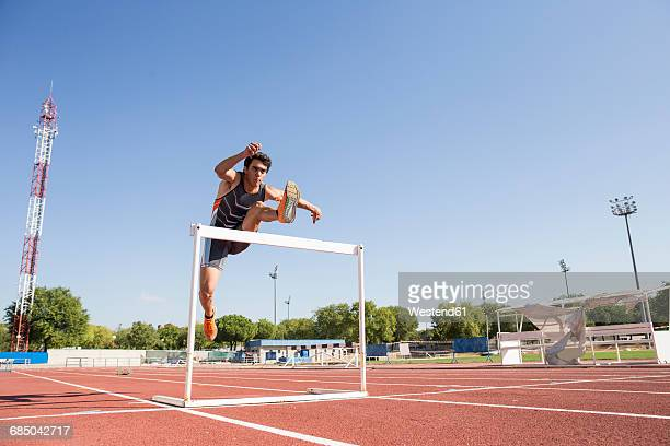 Athlete clearing hurdle during a race