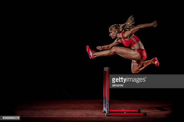 athlete clearing hurdle - athletics stock photos and pictures