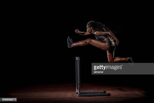 athlete clearing hurdle - hurdling track event stock pictures, royalty-free photos & images