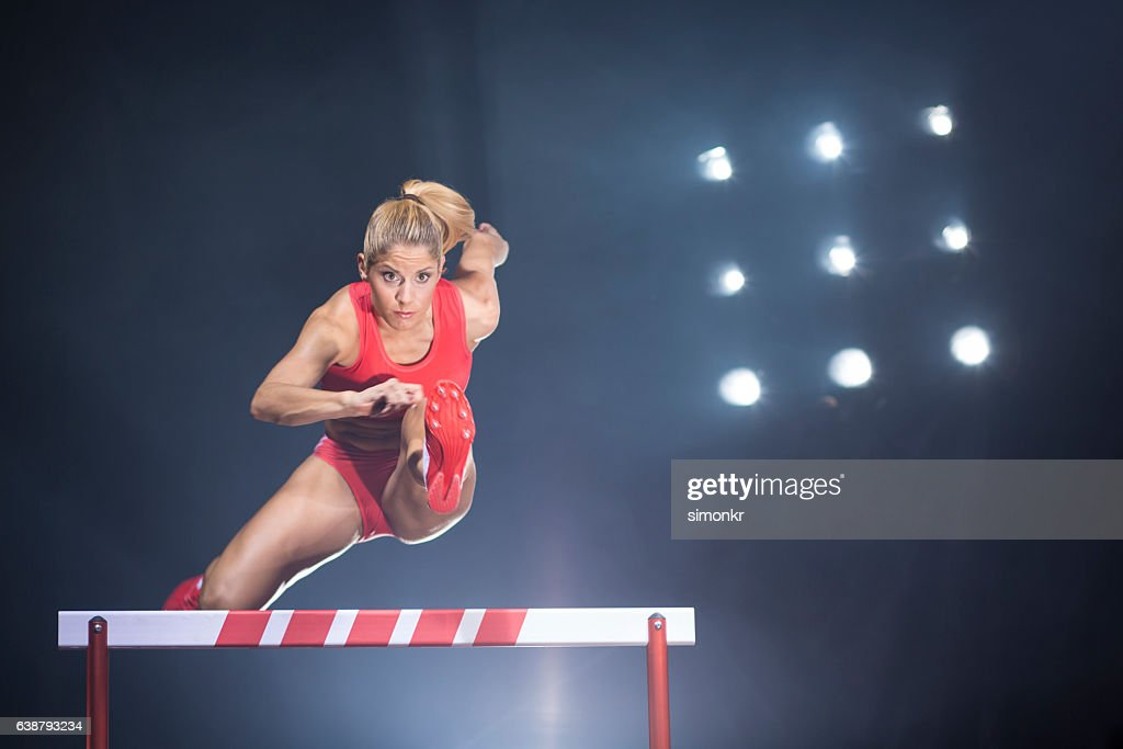Athlete clearing hurdle : Stock Photo