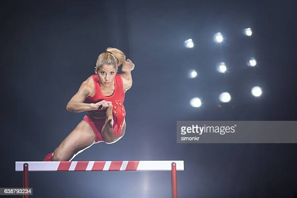 athlete clearing hurdle - hurdling stock photos and pictures
