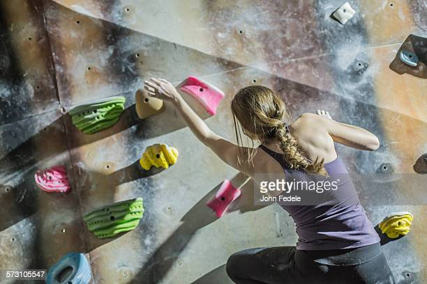 Athlete climbing rock wall in gym