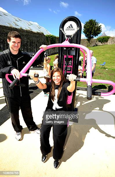 Athlete Craig Pickering helps with the outdoor gym equipment at the opening of the adidas London 2012 adiZone an outdoor gym facility on August 27...