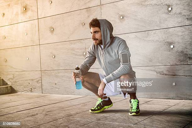 athlete crouched with a sport drink - sportswear stock pictures, royalty-free photos & images