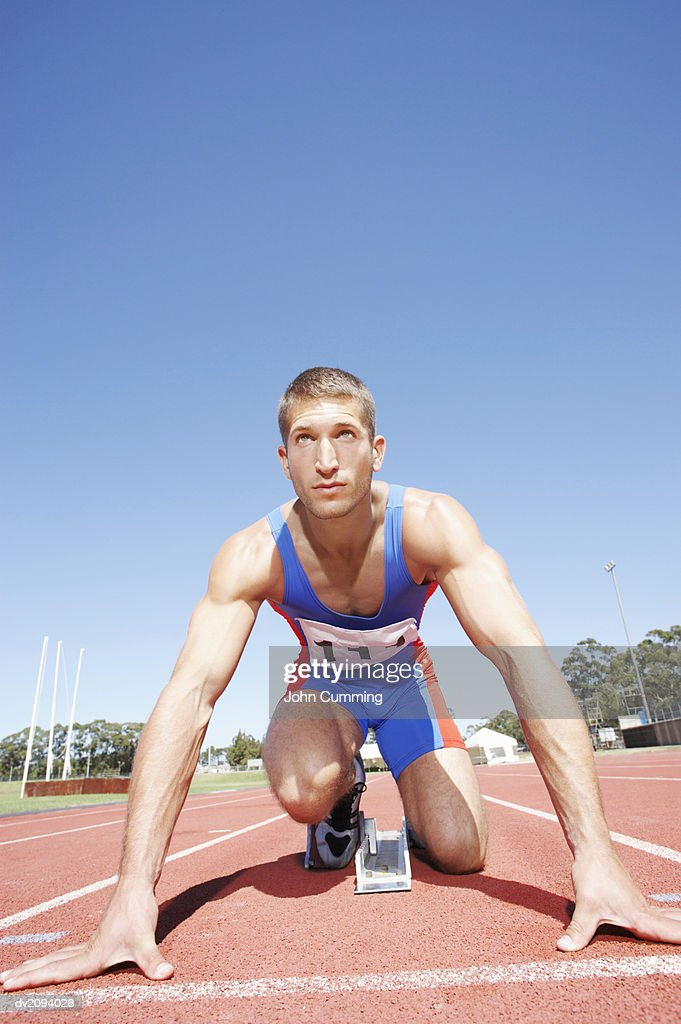 Athlete Crouching on the Starting Blocks of a Running Track : Stock Photo