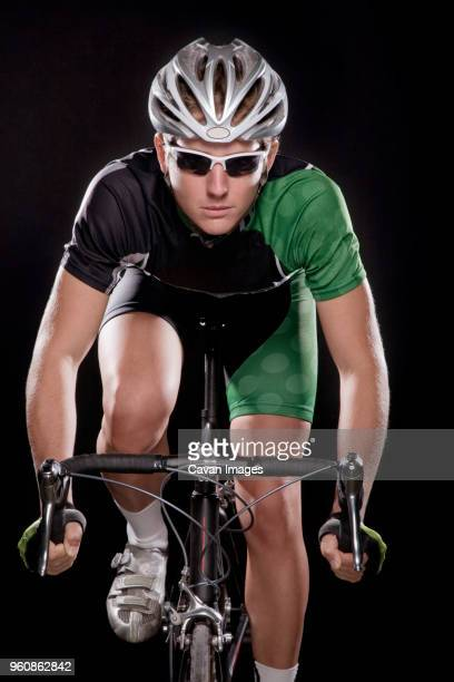 Athlete cycling against black background