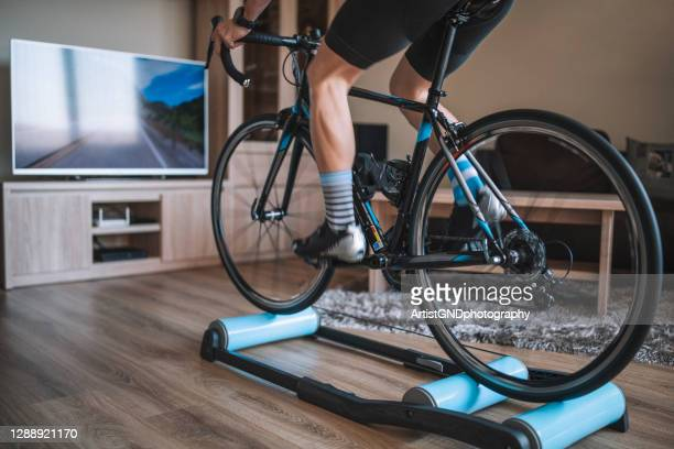 athlete cycling at home, sportsperson training with road bicycle at home. - peloton road cycling stock pictures, royalty-free photos & images