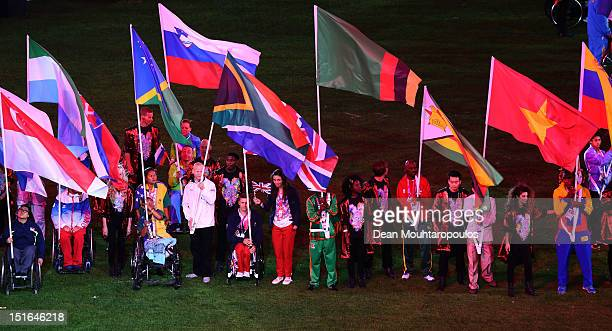 Athlete David Weir and cyclist Sarah Storey of Great Britain carry the flag join fellow flagbearers during the closing ceremony on day 11 of the...