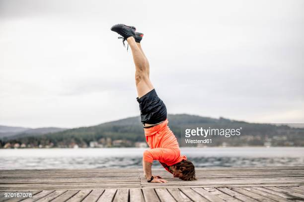 athlete doing a headstand on wooden deck at the lakeshore - carinthia stock pictures, royalty-free photos & images