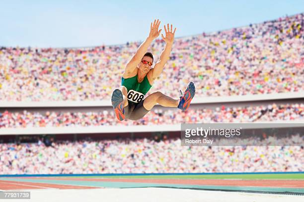 athlete doing a long jump in an arena - long jump stock pictures, royalty-free photos & images