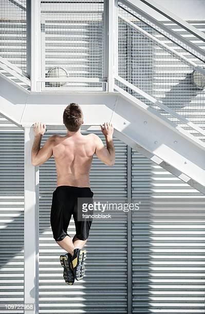 Sportler tun einem pull-up in einem urbanen Ambiente mit Kopie